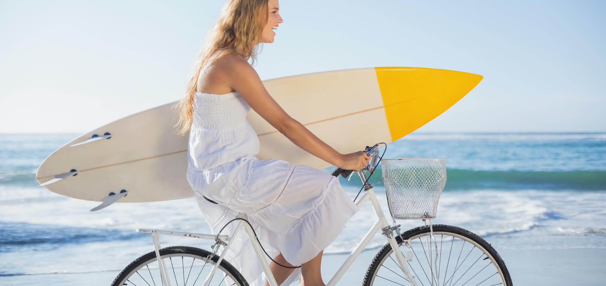 a carefree woman on a bike in front of the ocean, with a surf board under her arm