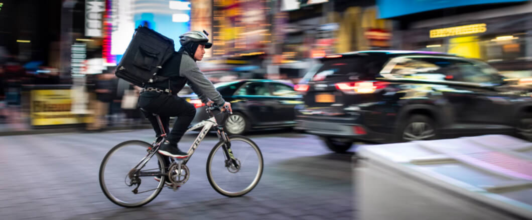A delivery rider on a bike on a busy city street at night.