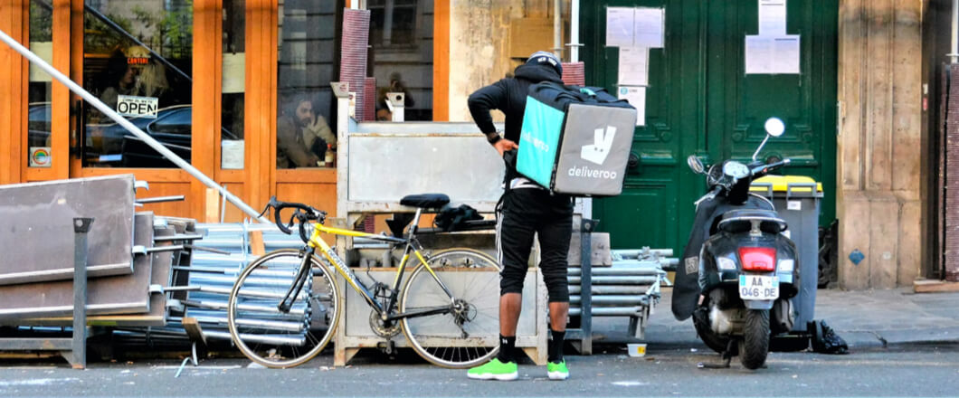 A Deliveroo worker standing next to his bike.
