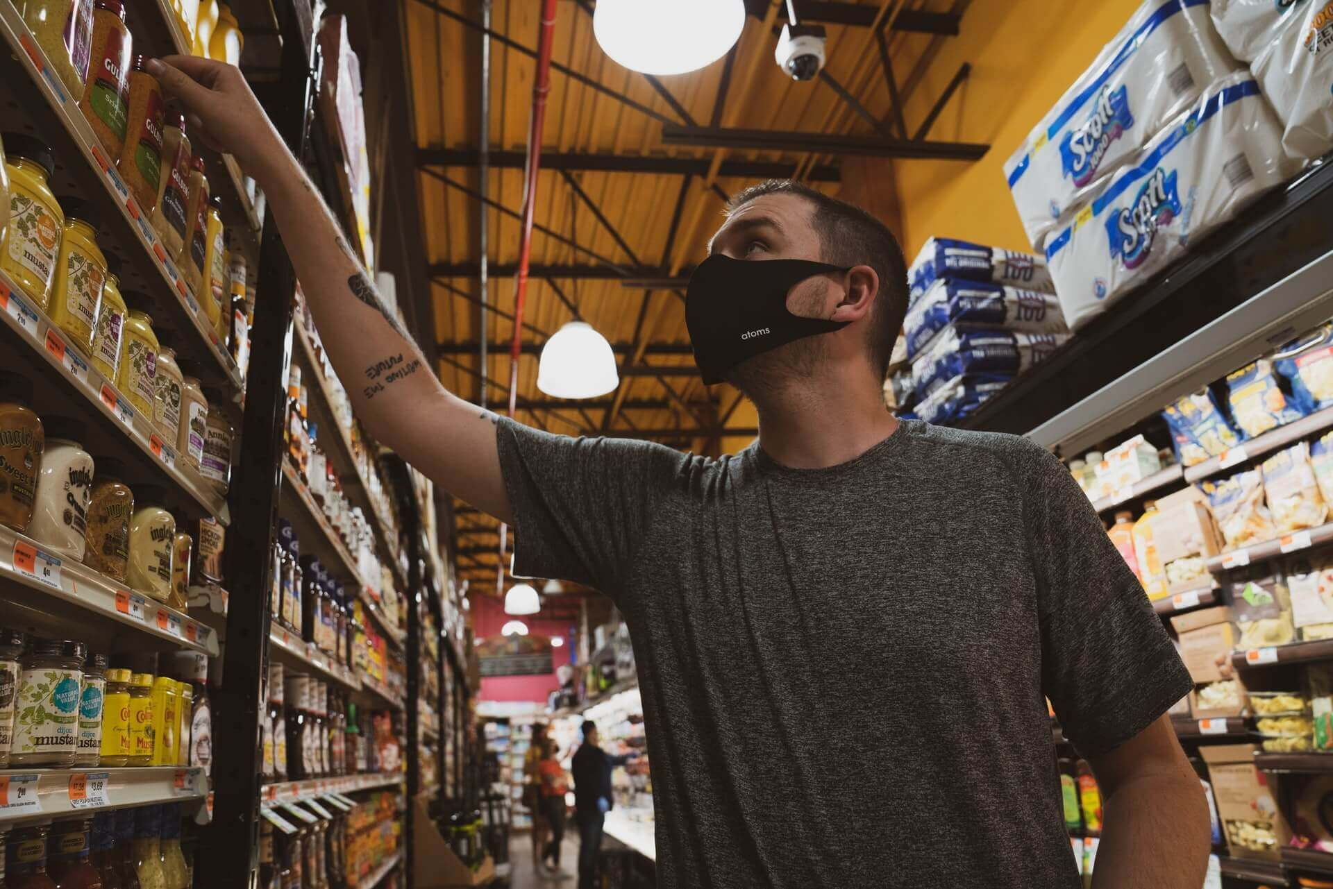 A man with a face mask shopping for groceries in a supermarket aisle