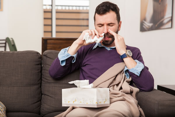 congested man using a nasal spray for his stuffy nose