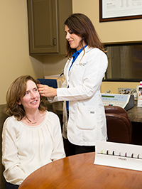 Dr. performing hearing test on patient