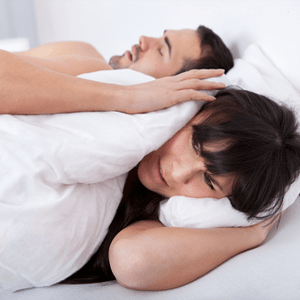 Woman holding her hands over her ears while man snores.