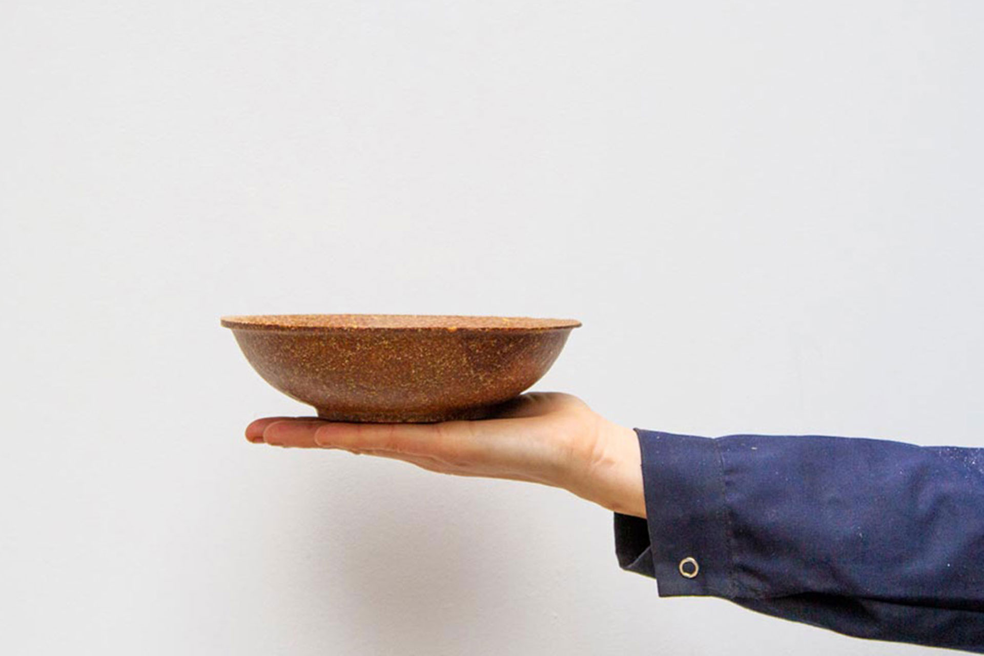 A hand holding a biodegradable bowl