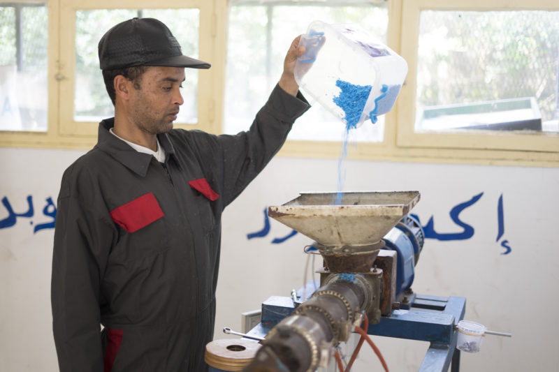 pouring plastic into extrusion machine