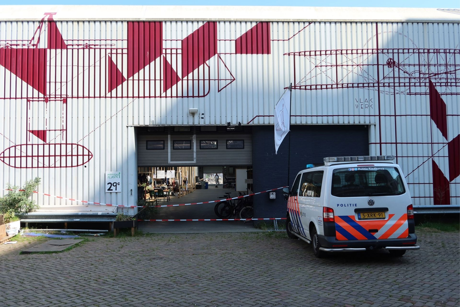 Eindhoven's workspace main entrance with caution tape around and a police car in front