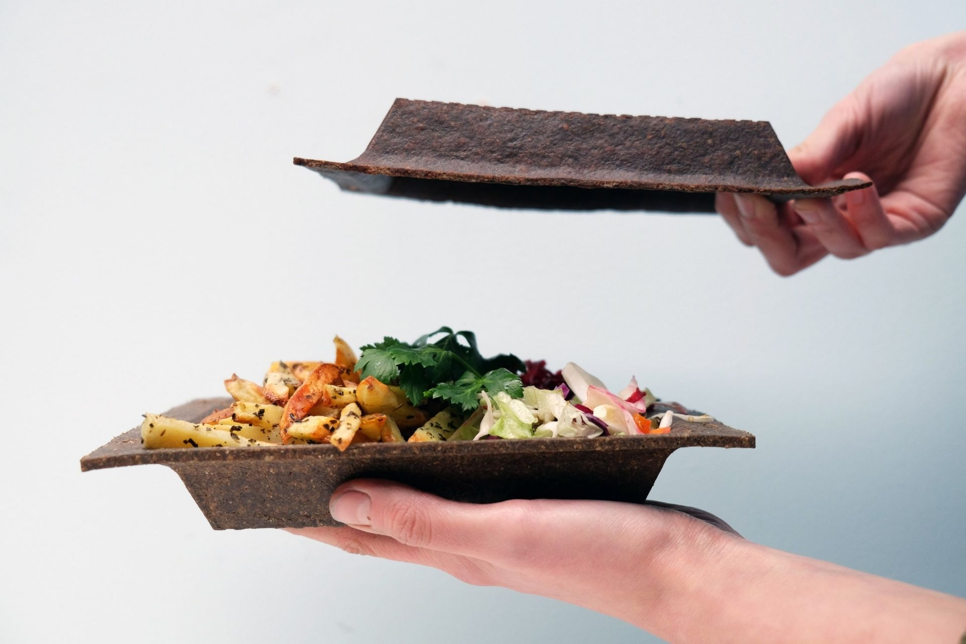 Hands holding Beyond Plastic wheat bran bowl with salad