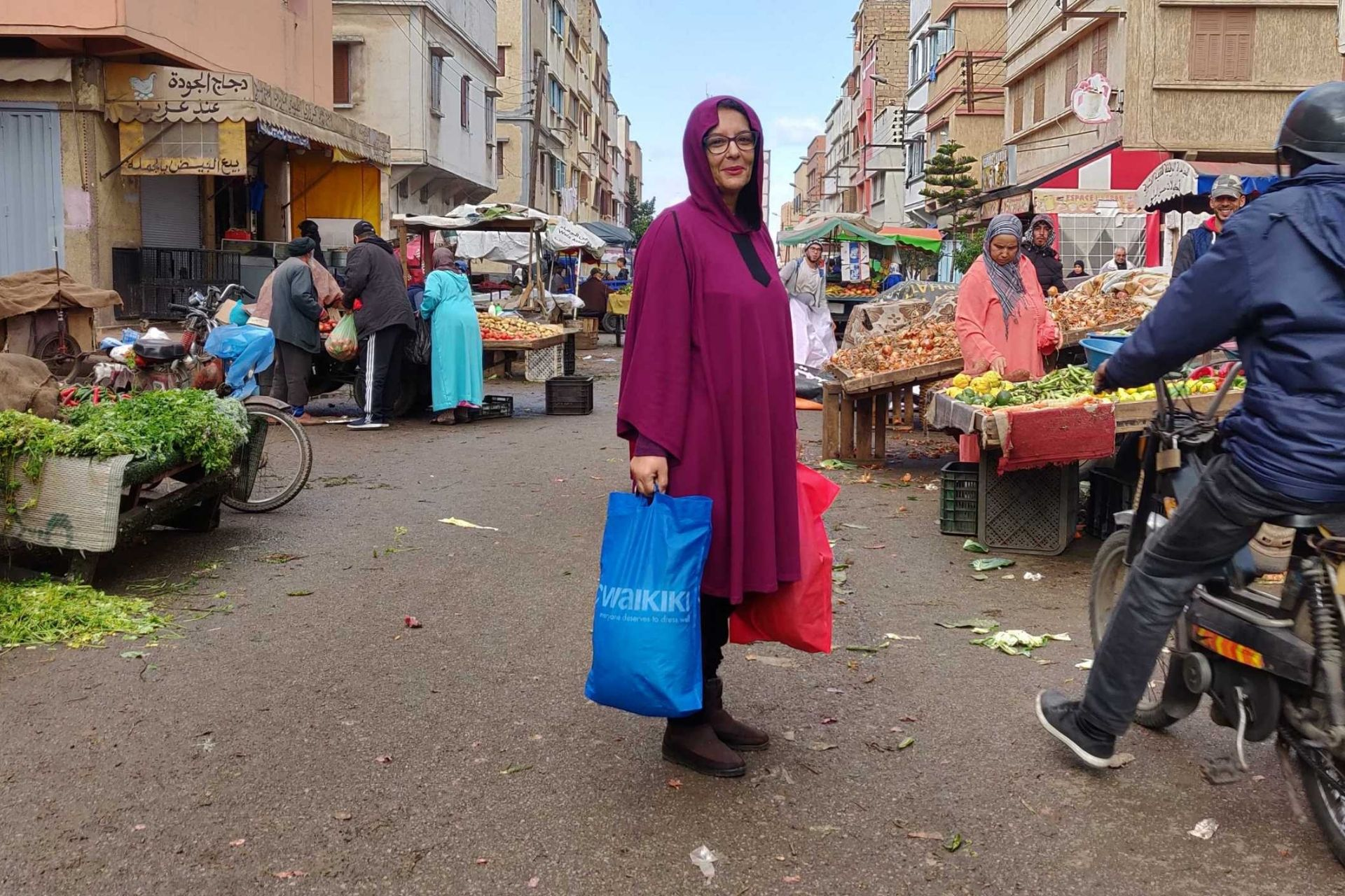 Woman standing in the middle of an asian street market
