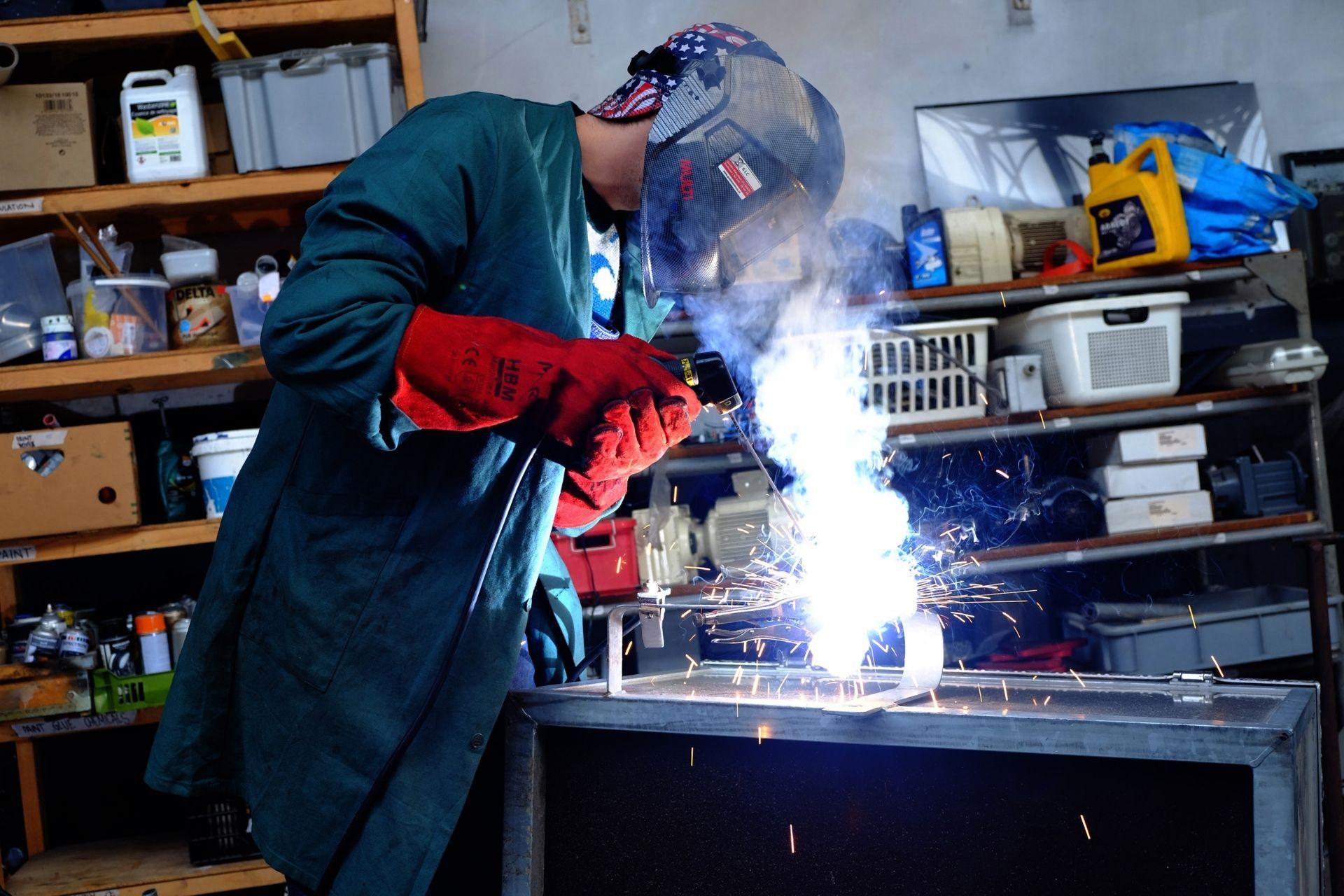 man welding in the precious plastic workspace