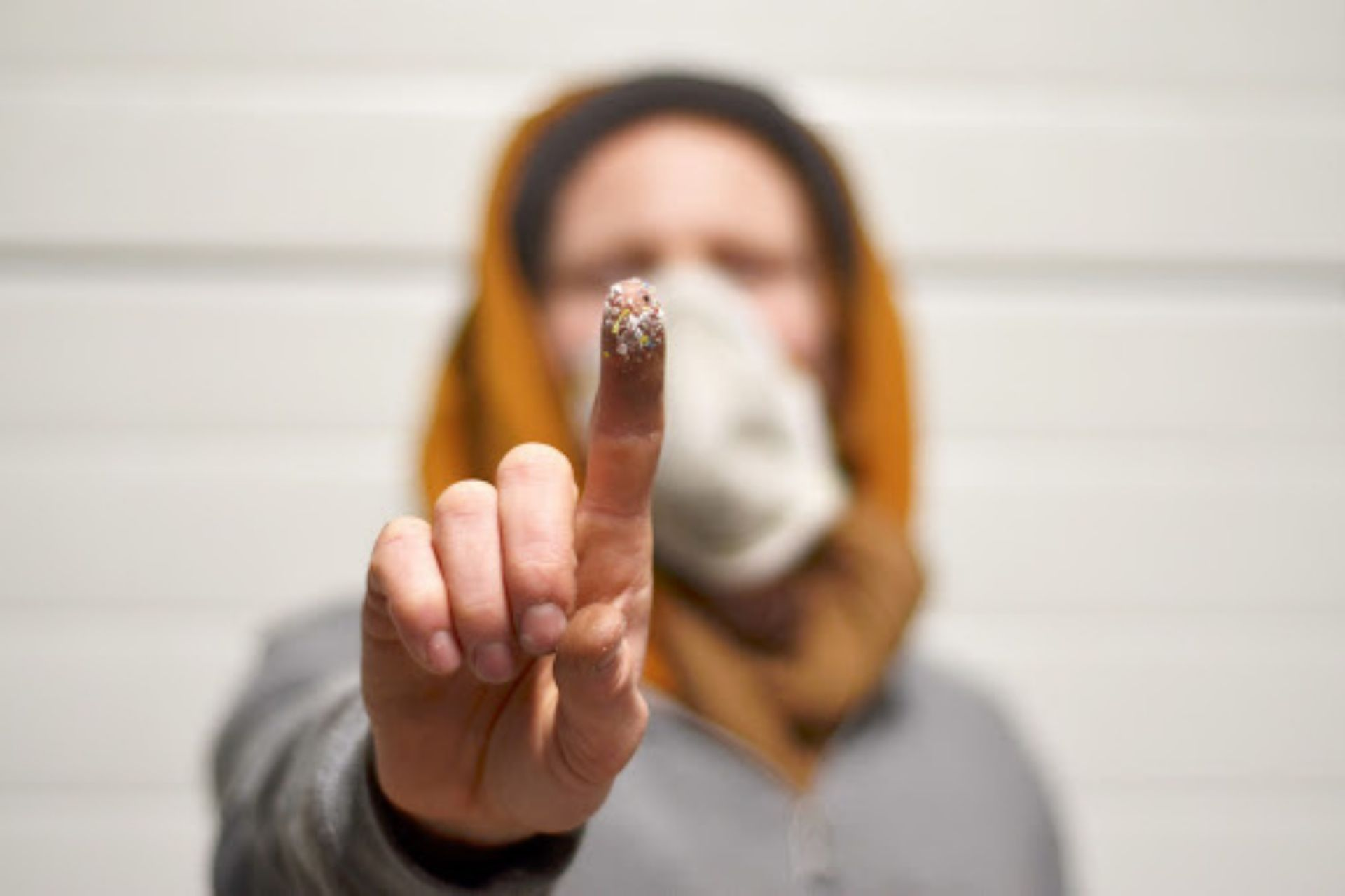 Man showing a microplastic on his finger