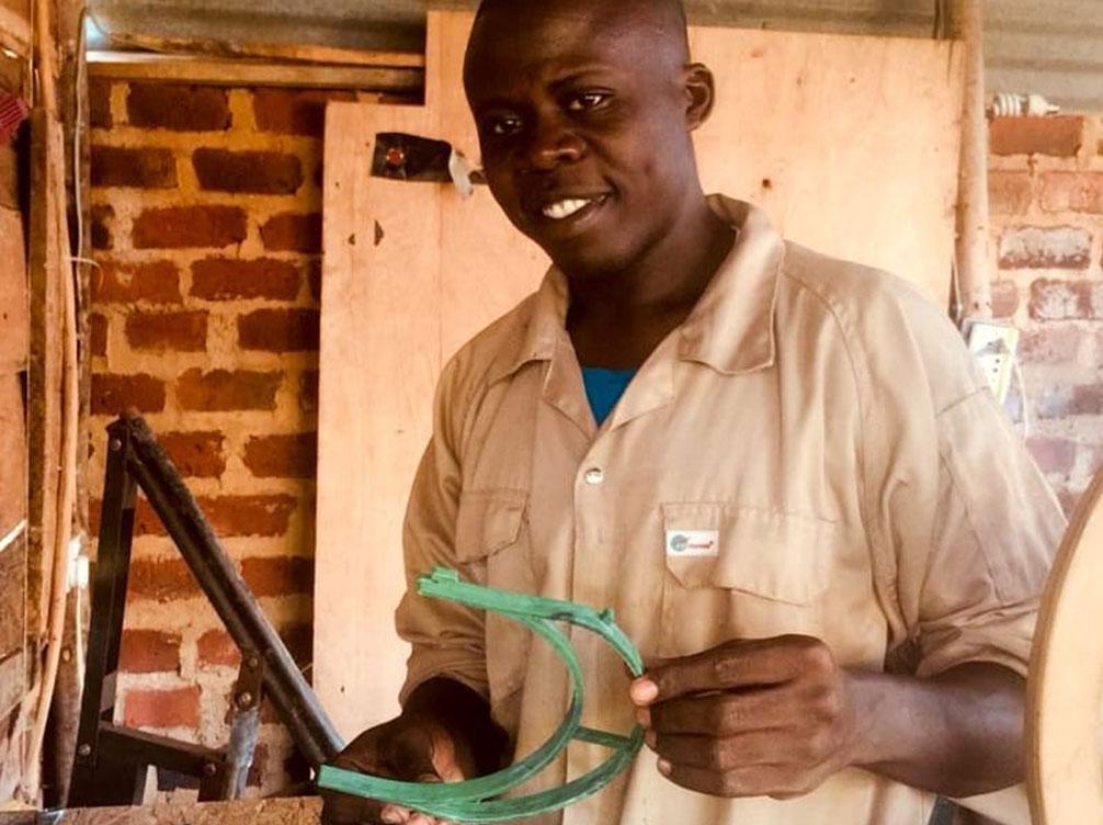 man holding a recycled face visor in uganda