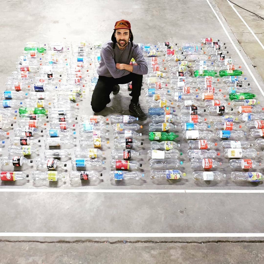 Man surrounded by plastic bottles