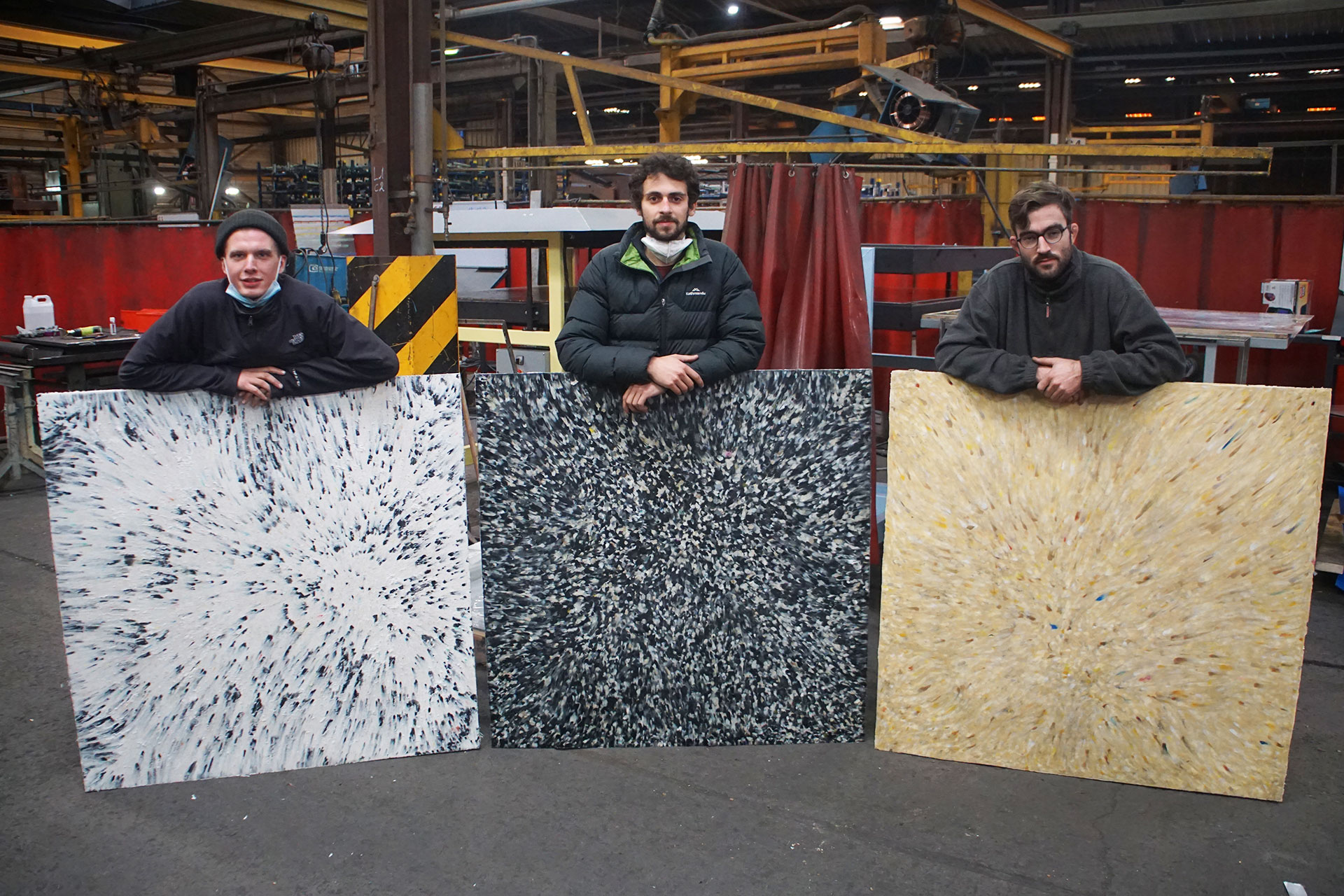 3 men holding colourful recycled sheets