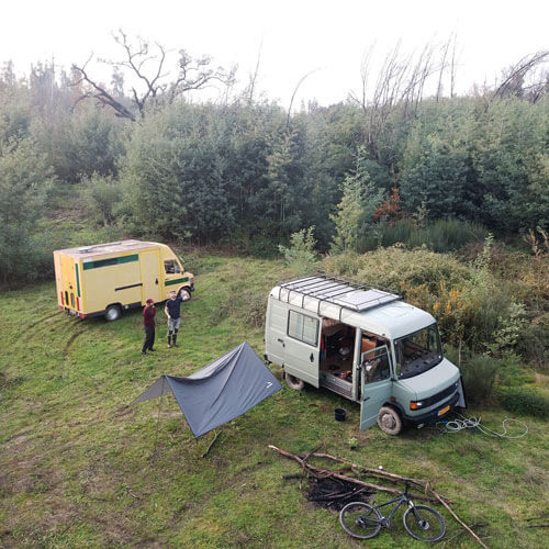 two vans and two man in a field