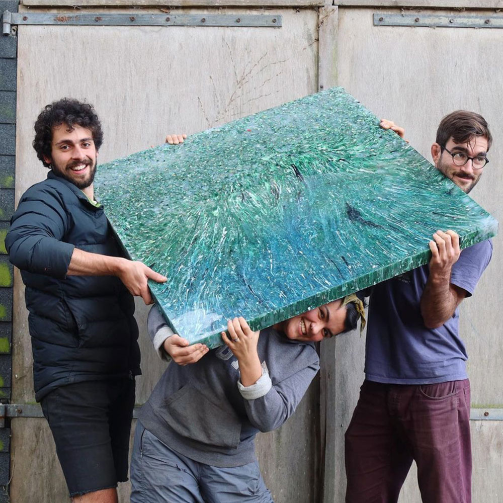 3 people holding a sheet of recycled plastic