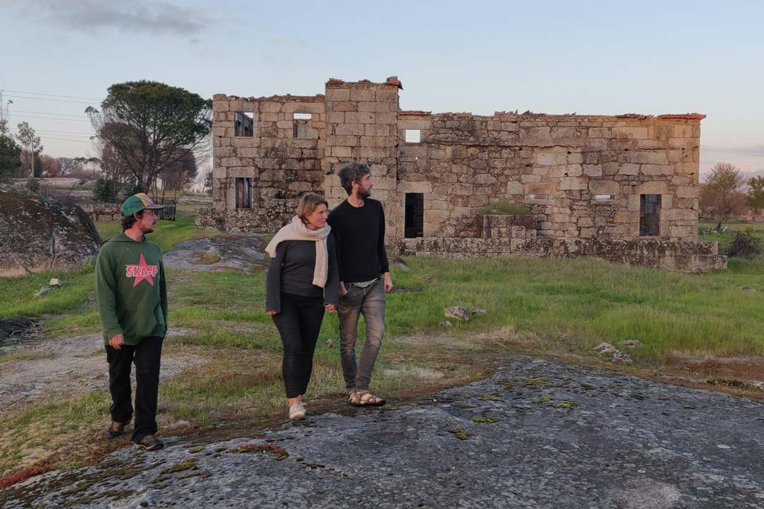 3 people walking in front of a ruin
