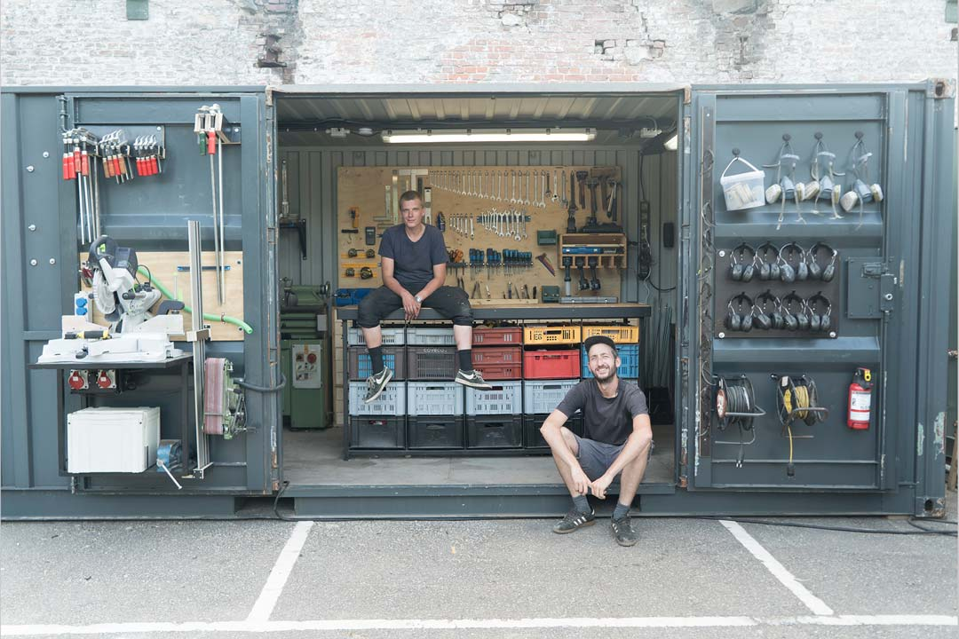 two men in front of a refurbished container