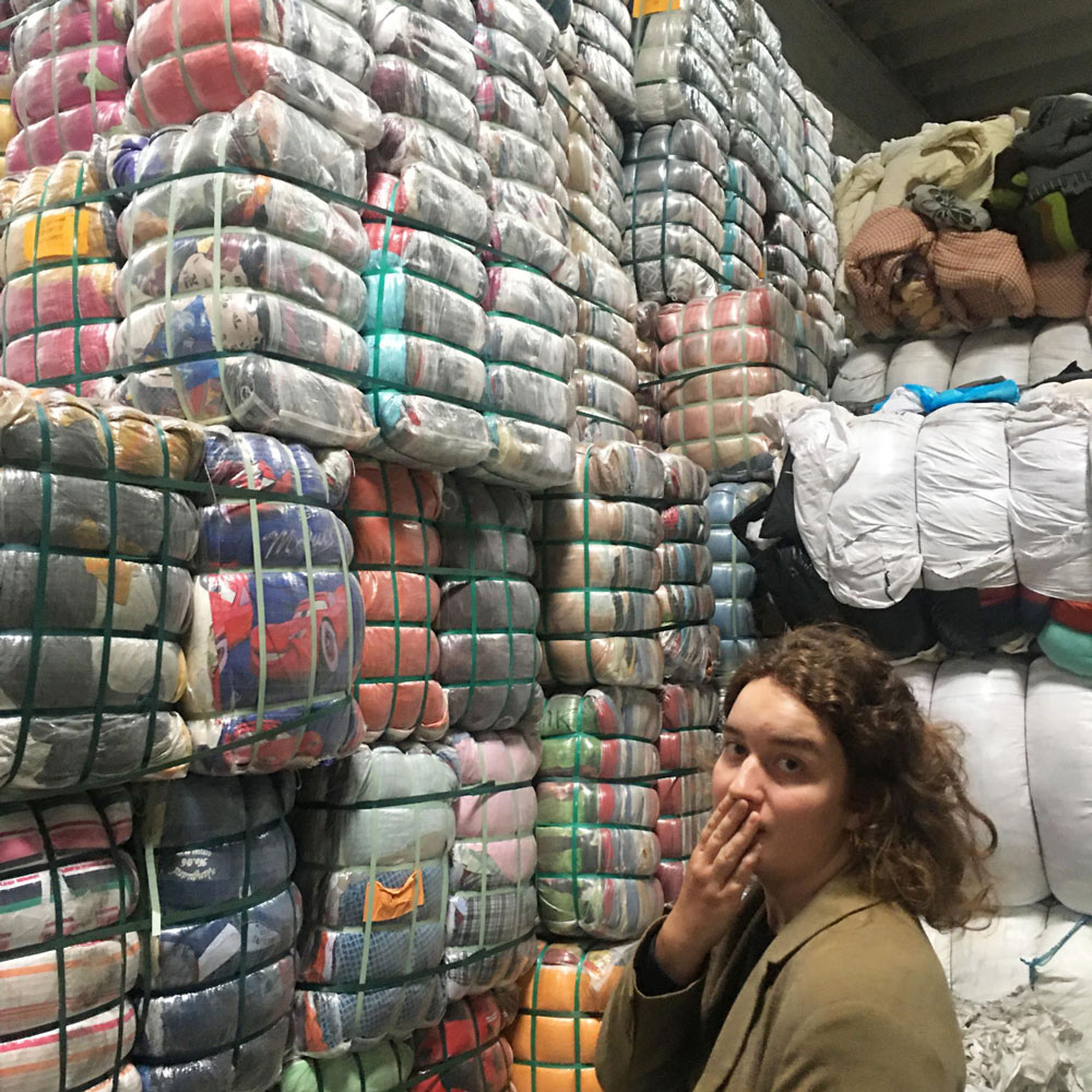 woman in front of a pile of recycled clothes