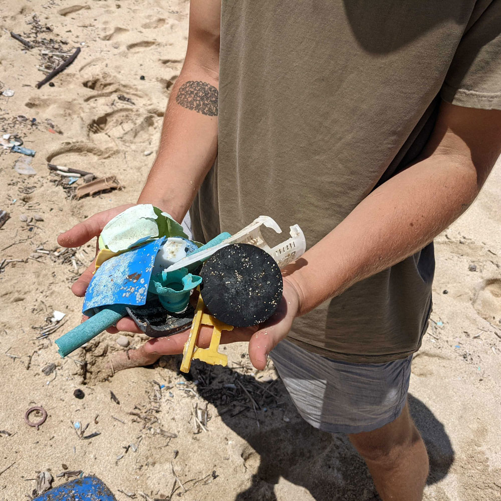 man on beach with plastic waste