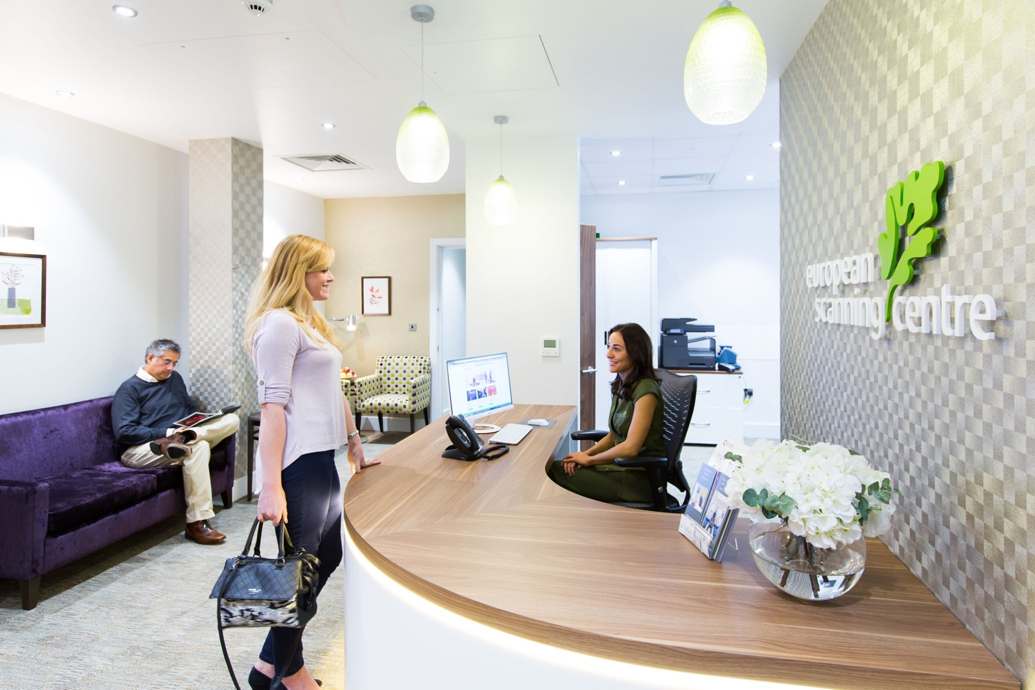 Patient greeted at reception desk by smiling member of staff