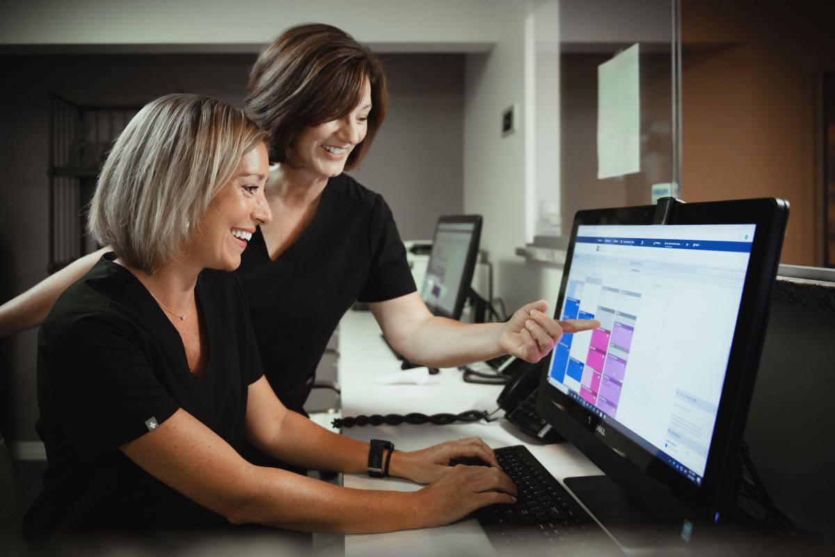 Photo of two team members working together on the computer