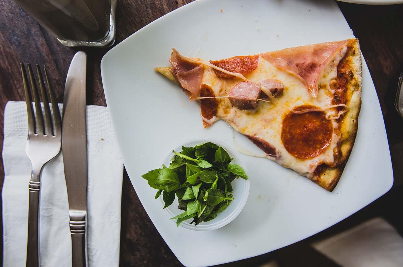 plaster pizzy na talerzu ze sztućcami