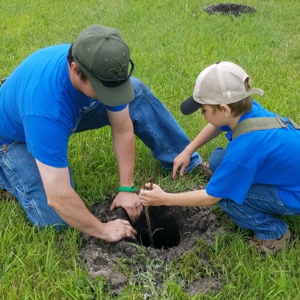 young man helping a child plant a tree