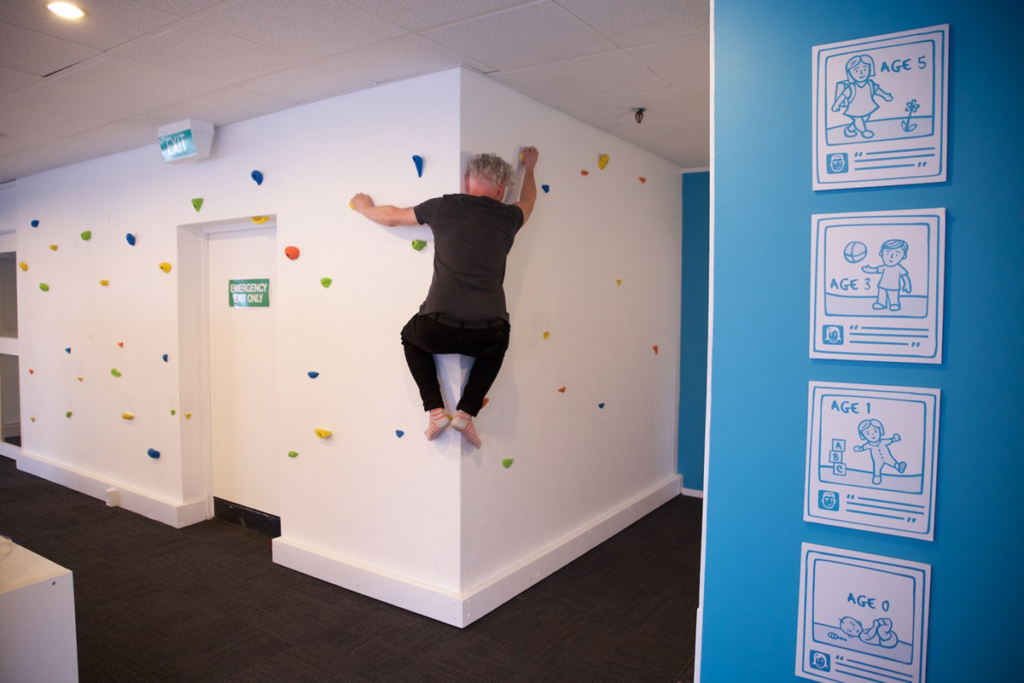 A male climbing a wall indoors