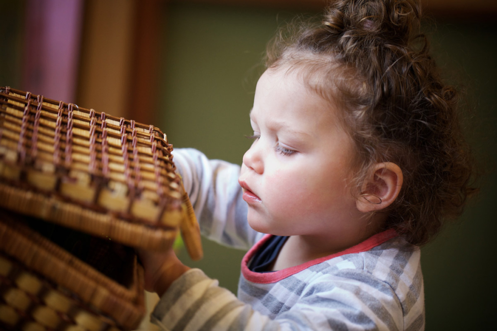 Toddler looking in a wooden basket