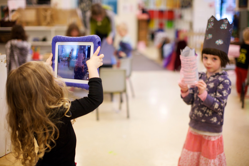 Toddler taking a photo of her friend with a tablet