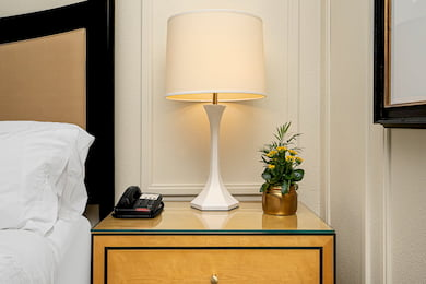 Southside King Bedroom - Bedside table with a lamp and phone.