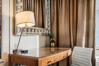 Southside Queen Bedroom - Desk with a white leather chair, lamp and a beautiful mirror.