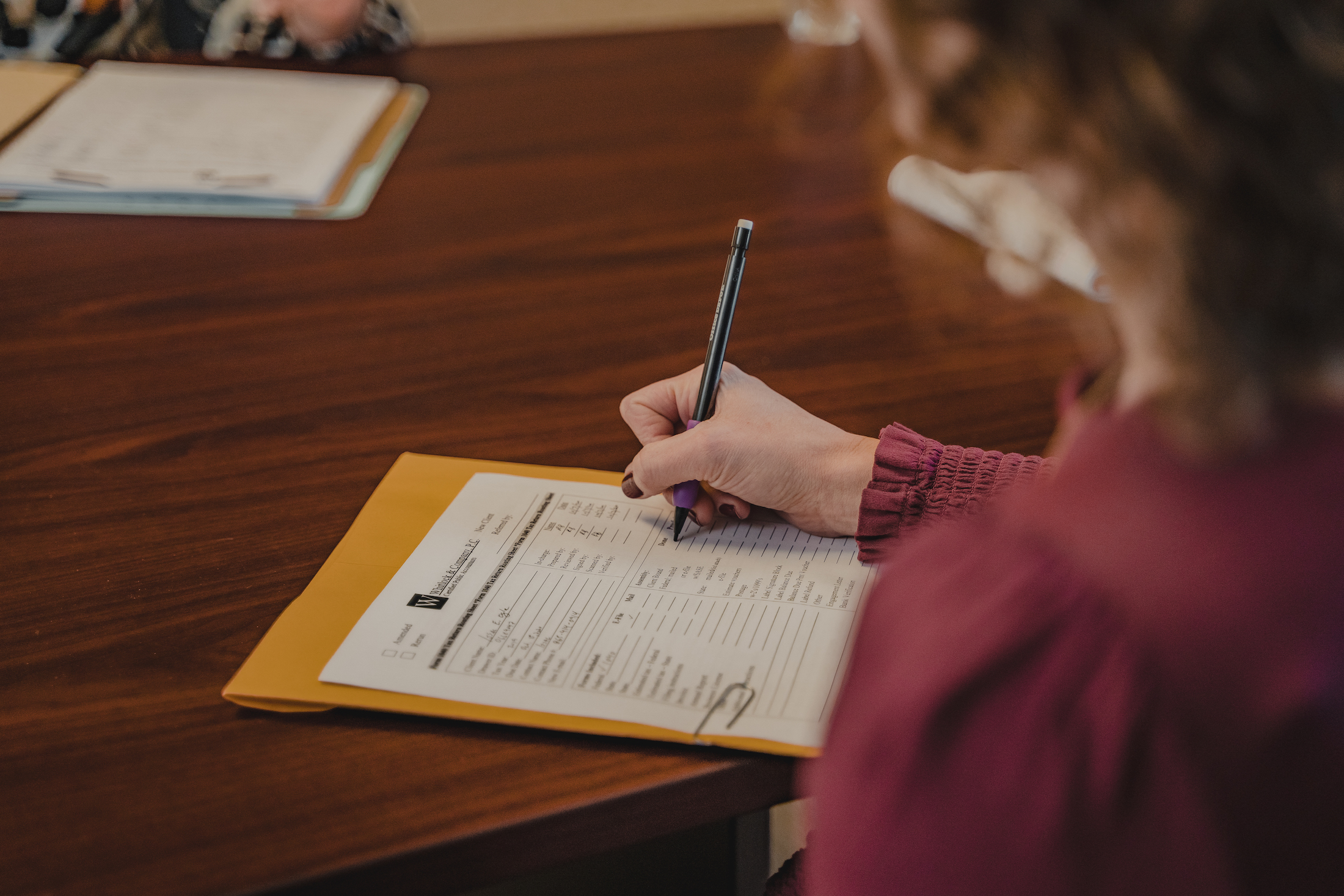 and employee at whitlock and company writing on a piece of paper related to personal accounting services provided at whitlock accounting services