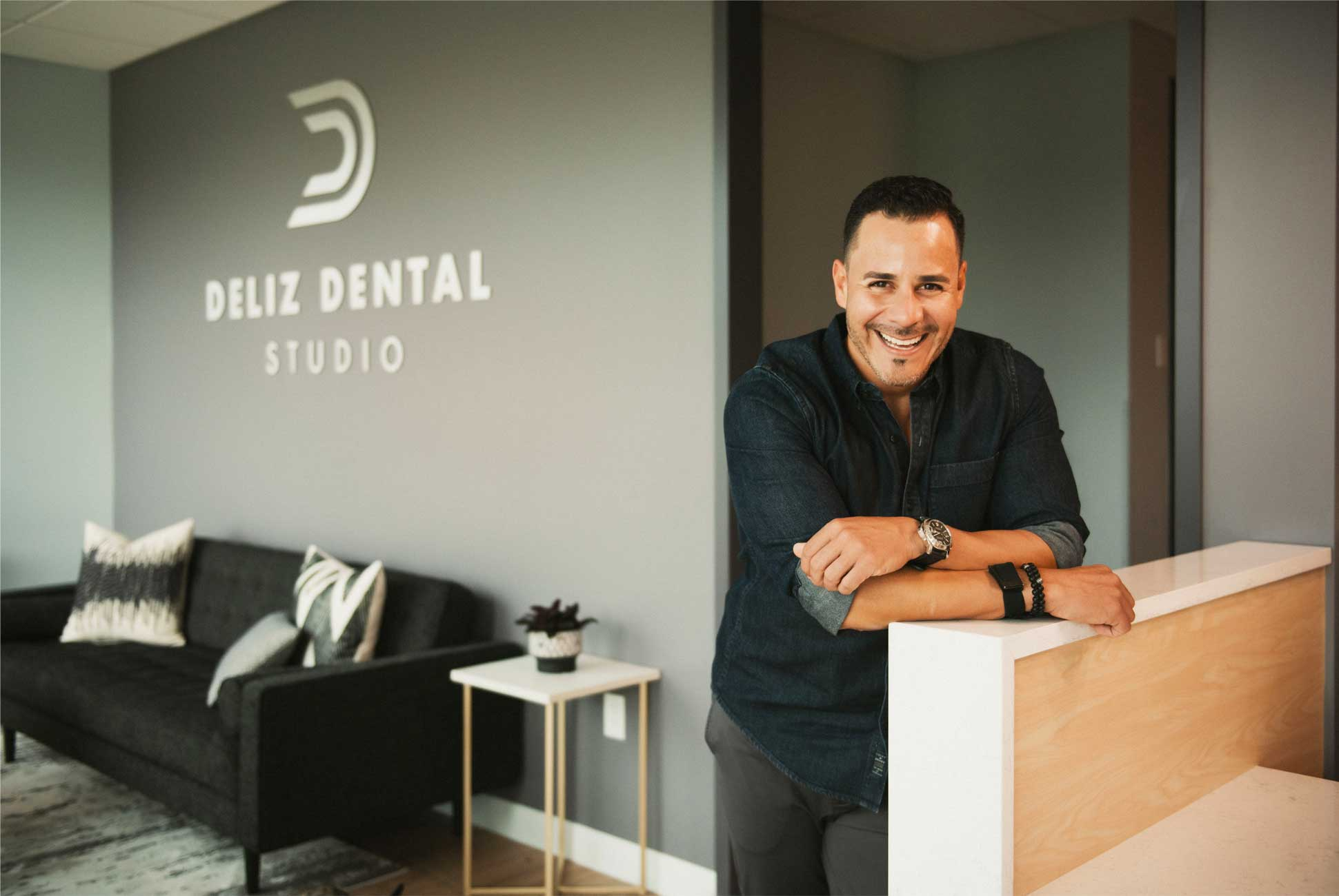 Photo of Dr. Deliz leaning against a counter and smiling