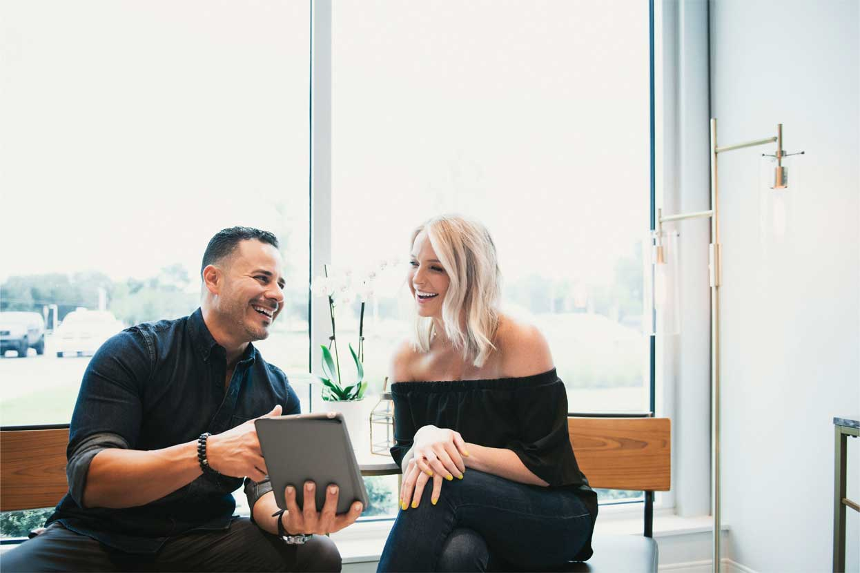 Photo of Dr. Deliz and a dental  patient smiling and  looking at an iPad