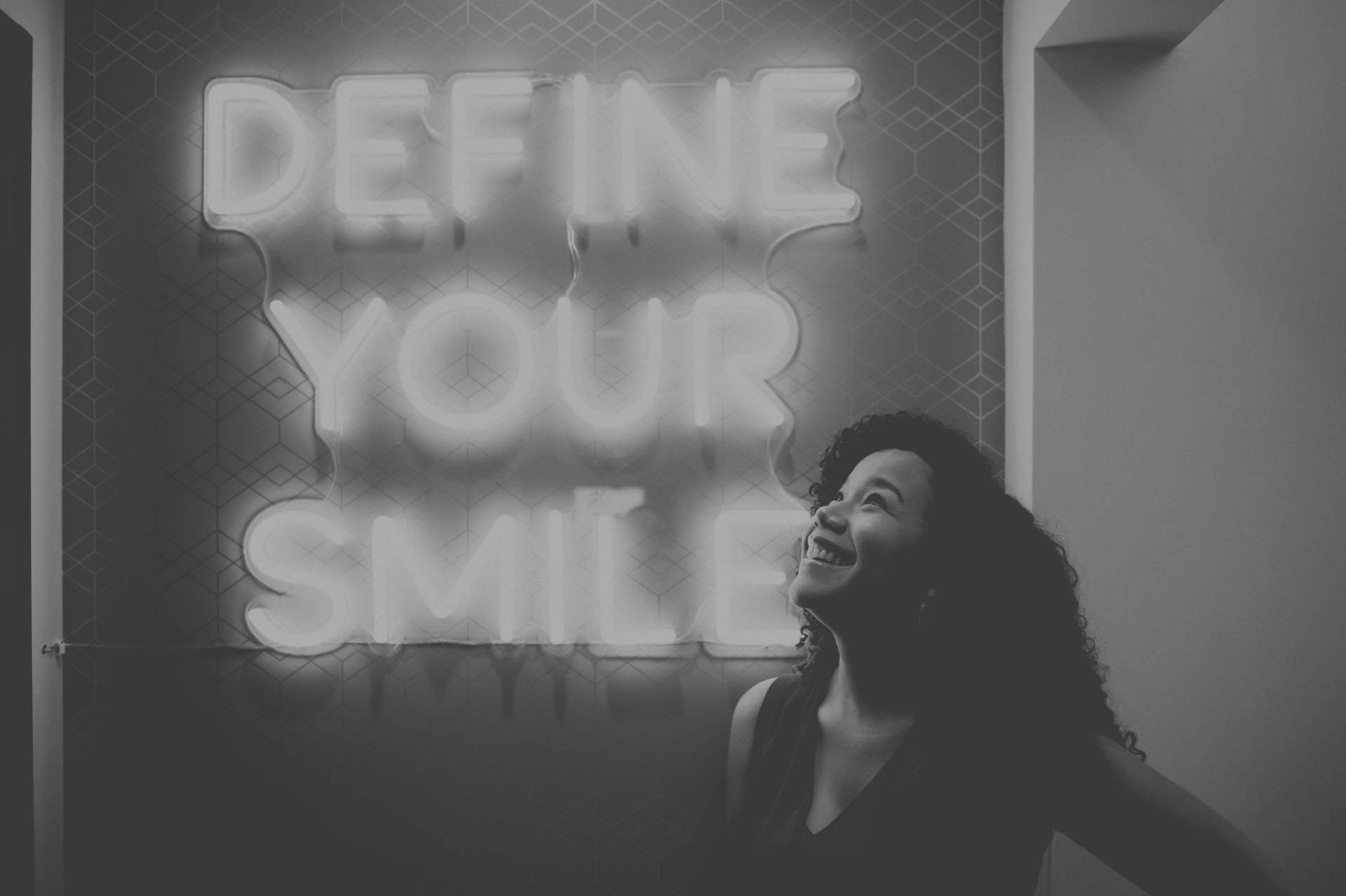"Photo of a young patient looking up at a neon sign which reads, ""Define your smile"""