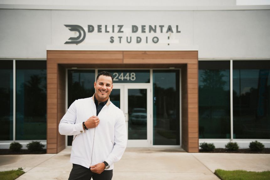 Photo of Dr. Deliz standing outside the front entrance to his practice