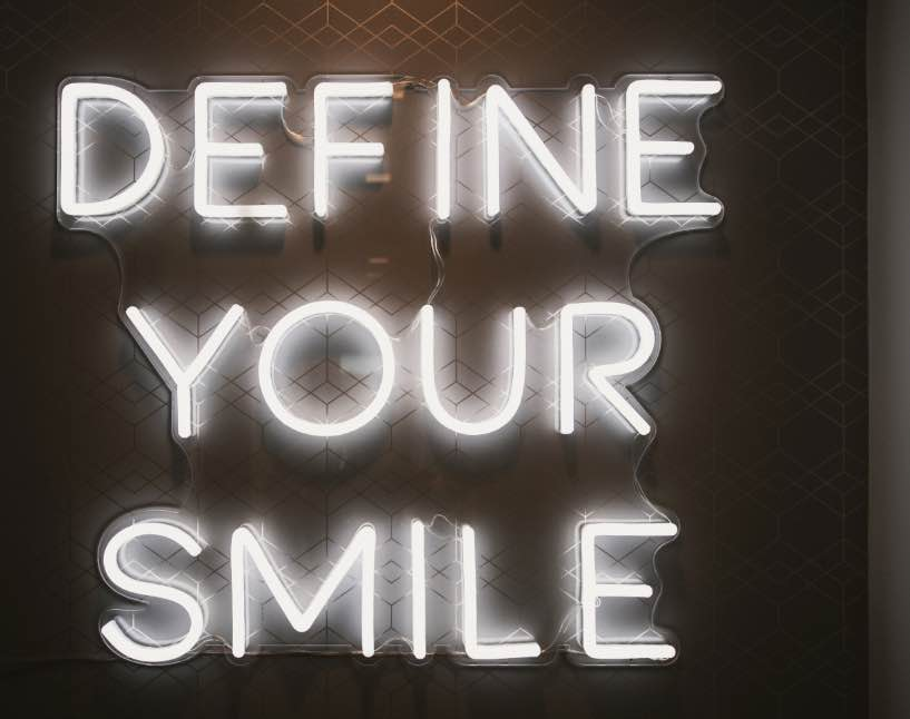 "Photo of a neon sign reading, ""Define your smile"""