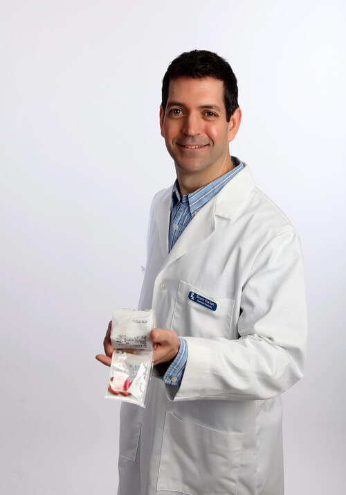 Pharmacist Bruce Kocian at Gibson Pharmacy holding a SyncRx personalized medication pack