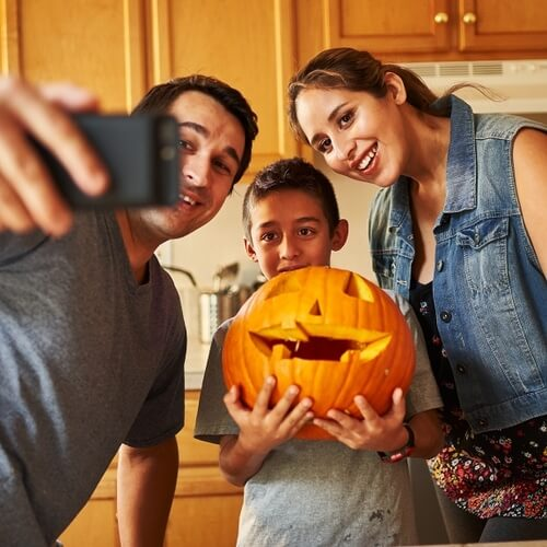 Family taking a selfie, while holding a carved pumpkin.