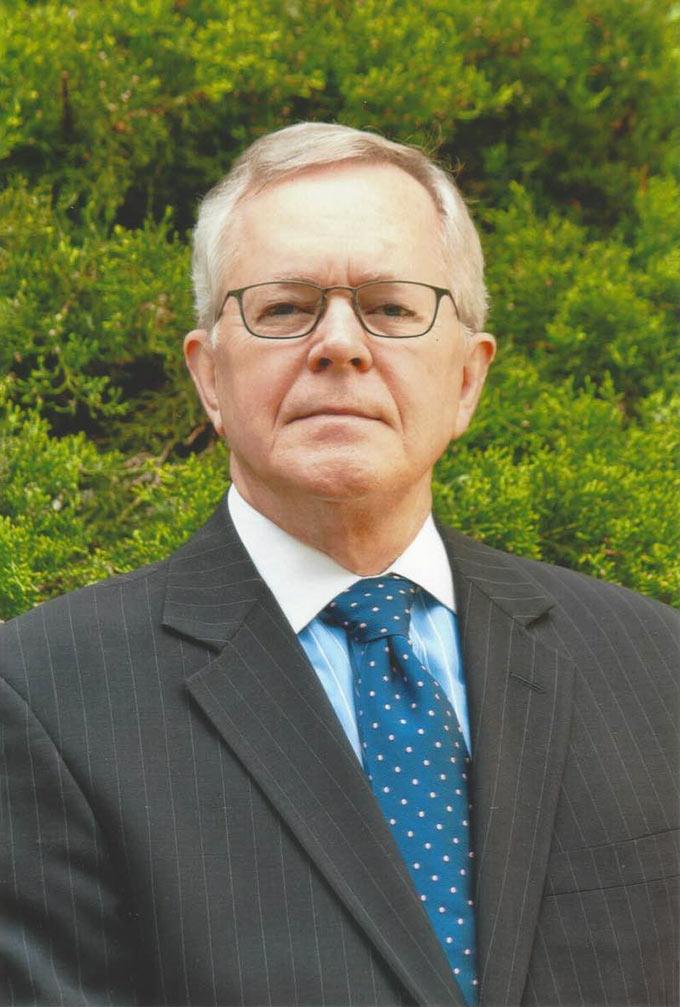 Portrait photo of Burton Dunbar in front of foliage