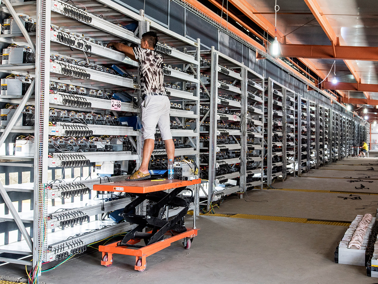 Bitcoin mining farm. Thousands of BTC mining rigs are placed on a shelf.