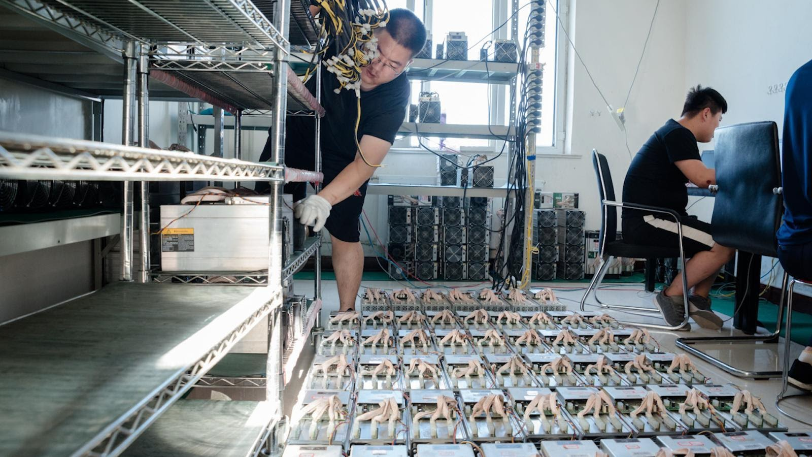 Two miners are working on maintaining their mining rig