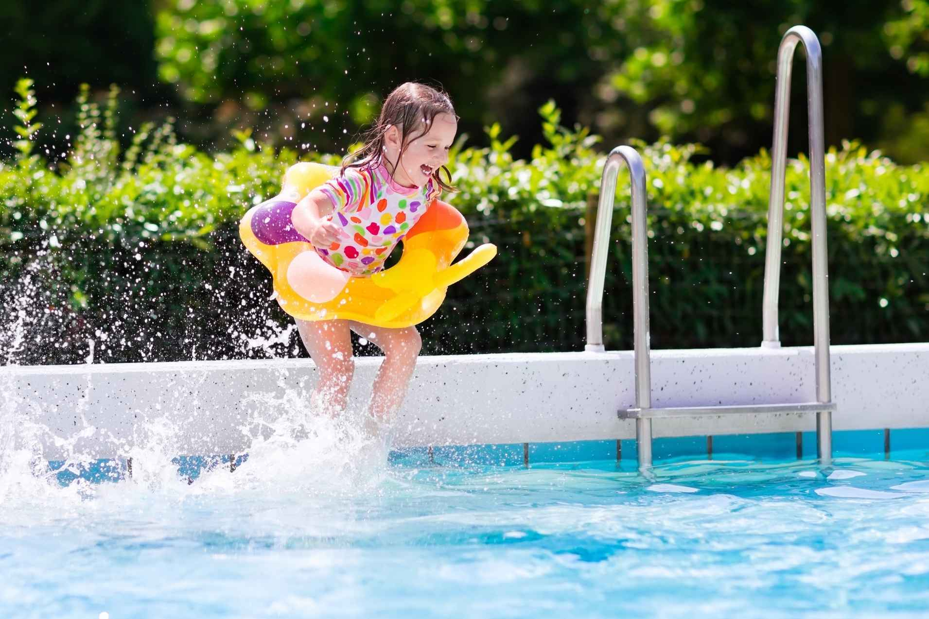 Little girl jumping into pool.