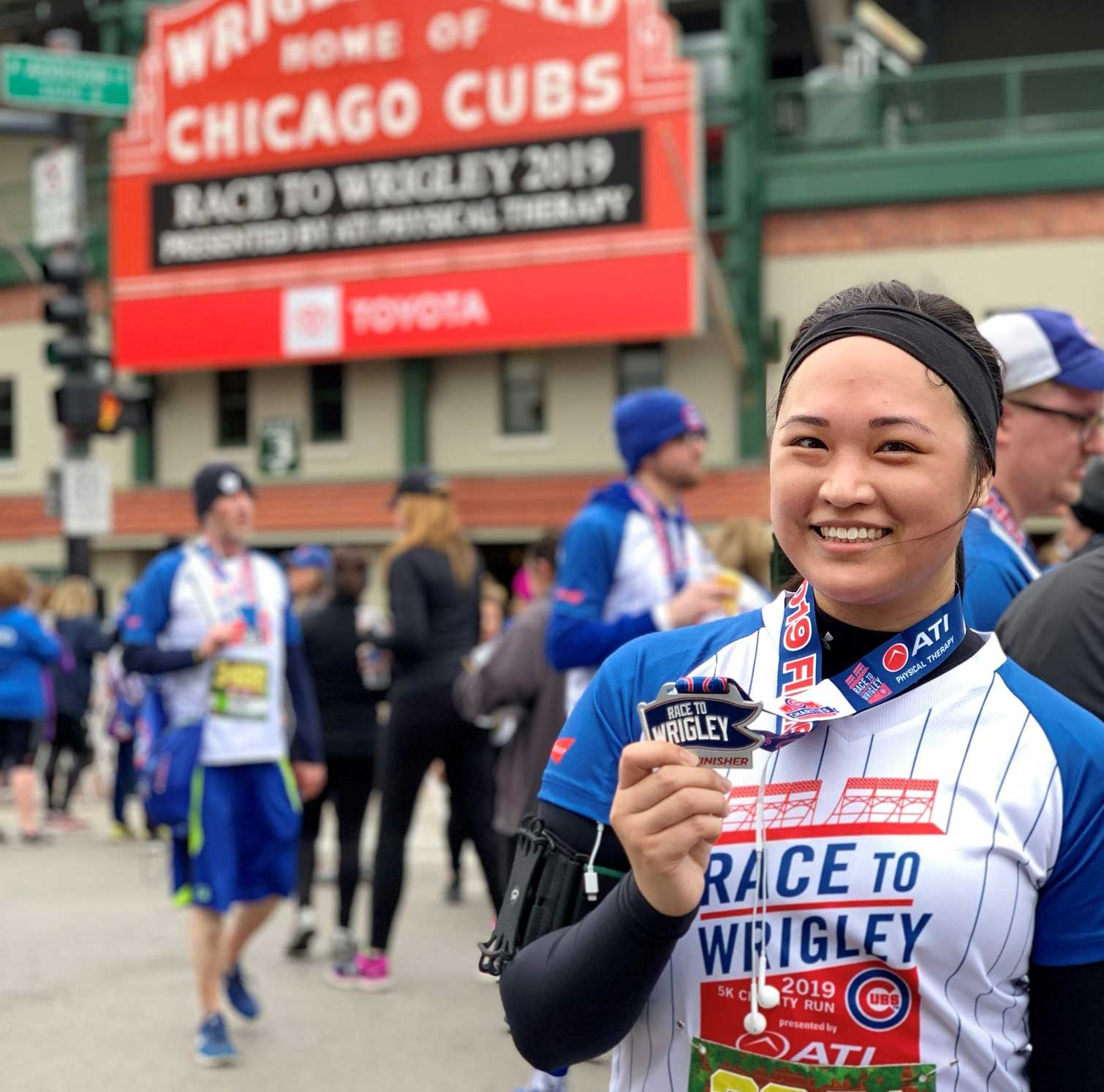A woman posing in front of the Wrigley Field with a medal from a marathon run