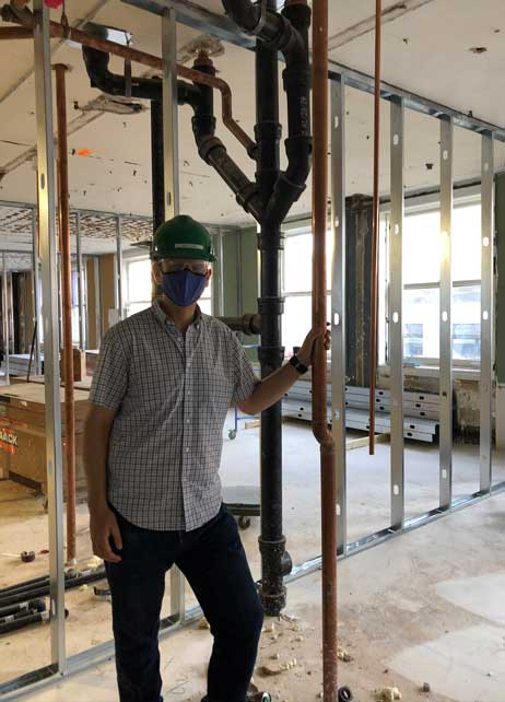 A single construction worker in a space with the basic structure of a room built out.