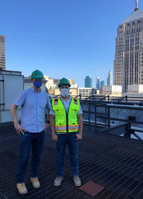 Two men in hardhats and person protective equipment on a rooftop.