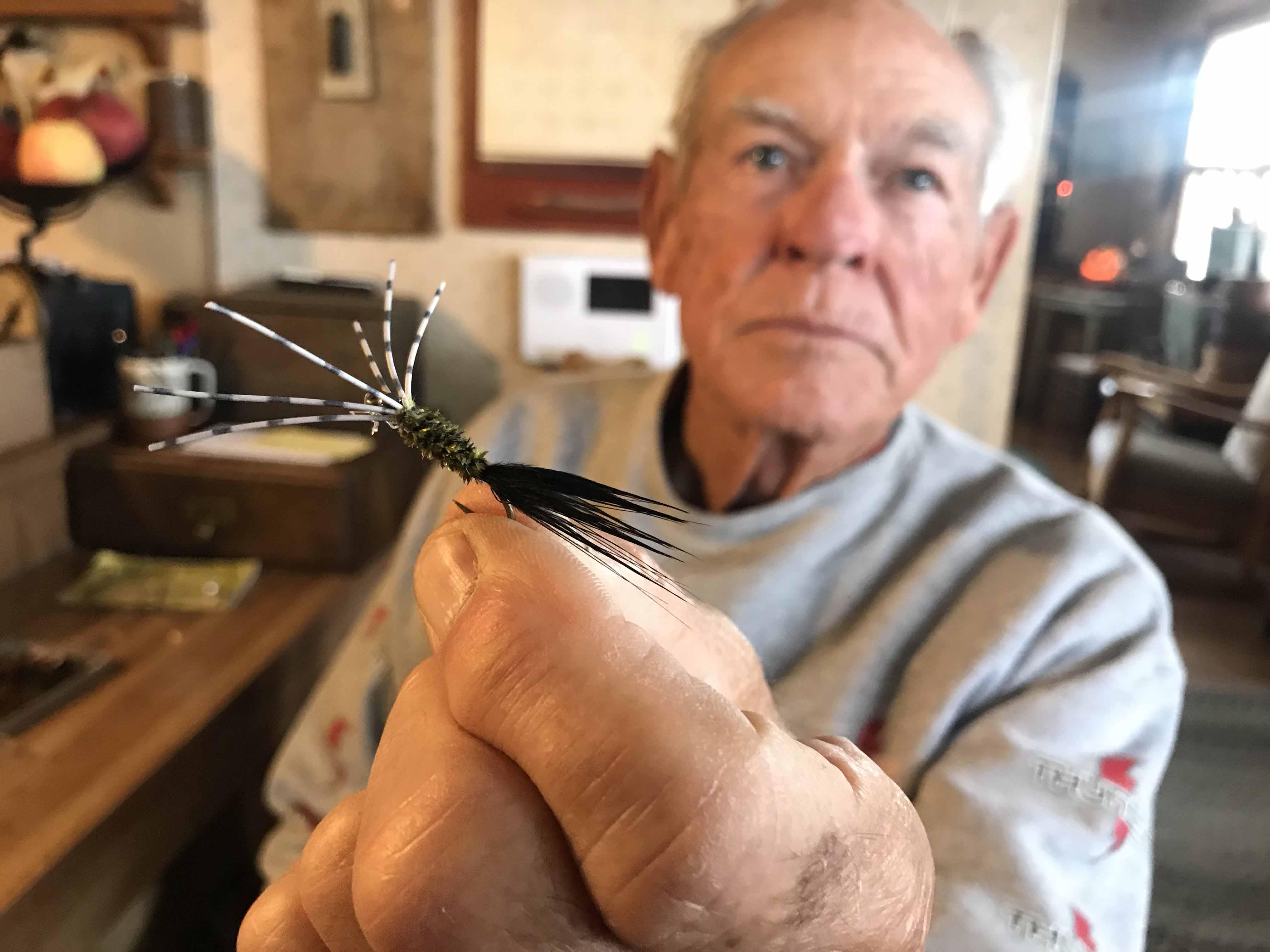 John Branshaw holding up a fishing lure close to the camera.
