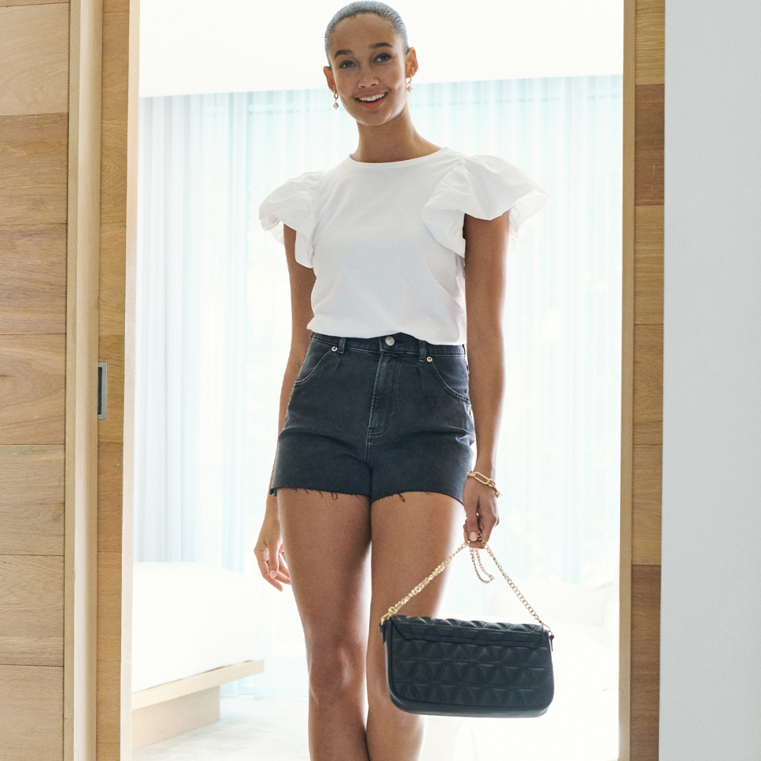 model with sleek bun wearing a white top with ruffle sleeves and black denim shorts carrying a small black handbag