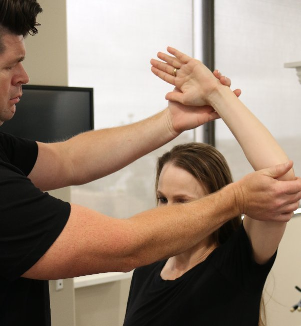 Dr. Beau applying pressure to a patient's shoulder